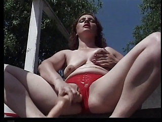 A plump red head slut masterbates outside on the deck