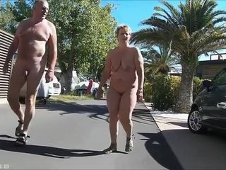Mature couples walk around the naturist resort downright bare