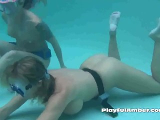 2 nude nymphs breath holding underwater in pool